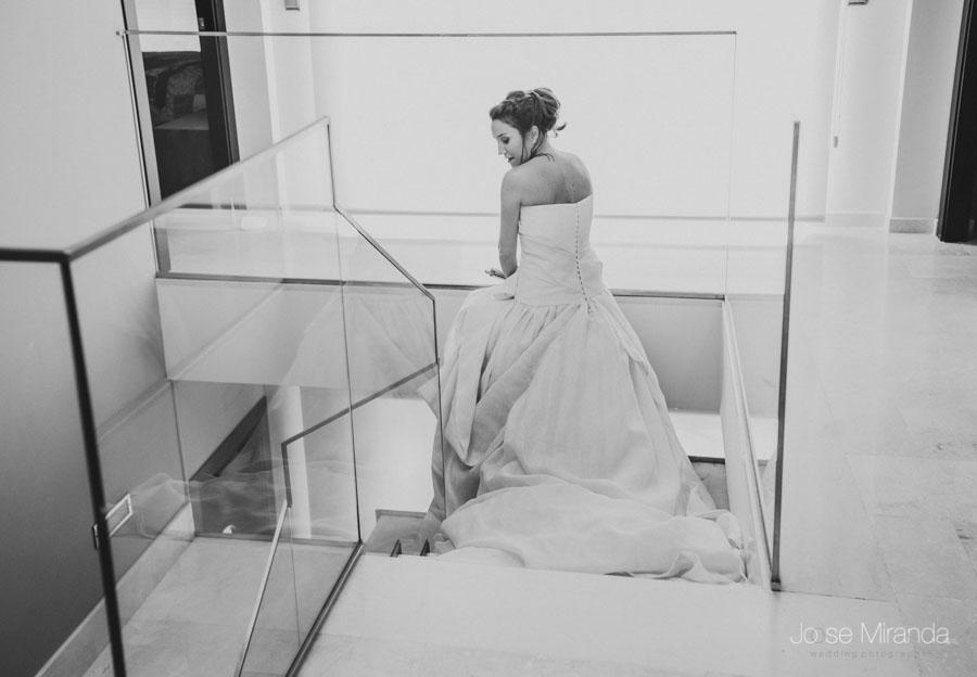 retrato en blanco y negro de novia con vestido palabra de honor y falda con volumen. detalle de la cola
