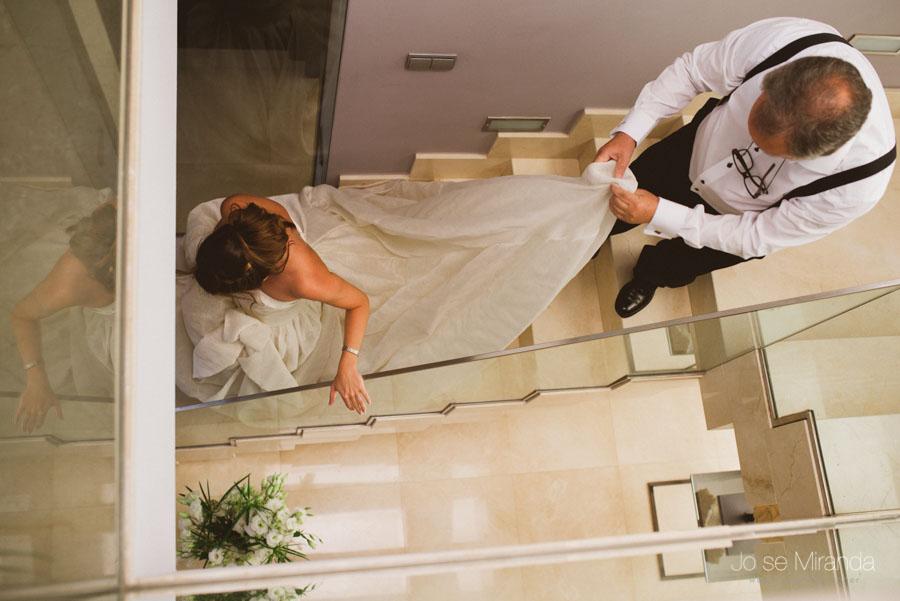 novia bajando la escalera mientras su padre le lleva la cola