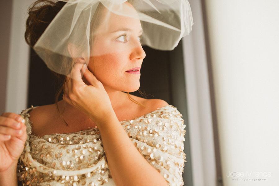 retrato de la novia poniéndose el pendiente con tocado de tul