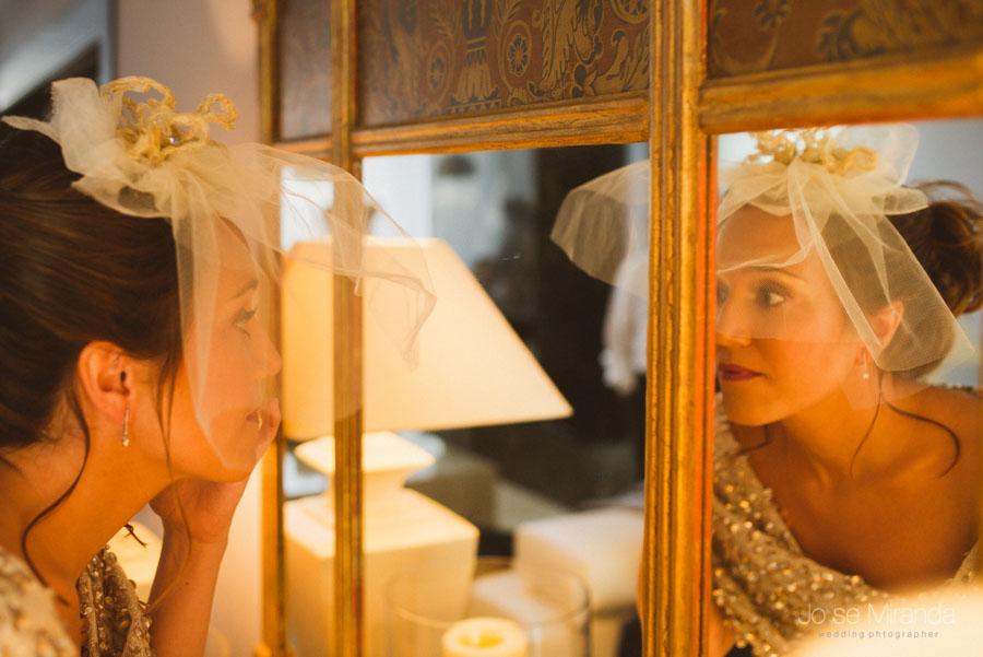 novia mirándose al espejo con tocado de tul de jesús peiro