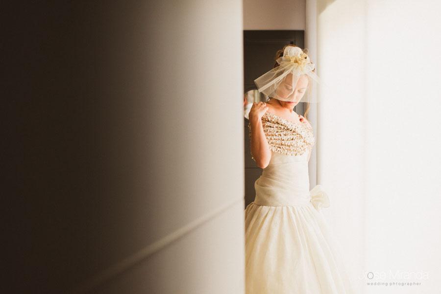 retrato de novia con tocado de tul y estola de lentejuelas doradas
