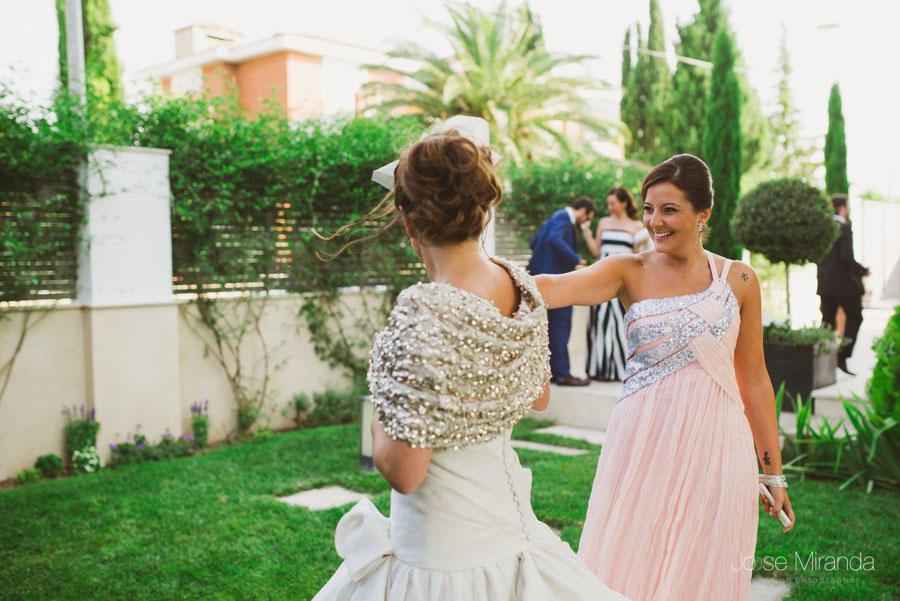 novia y amiga saludándose con vestidos de lentejuelas