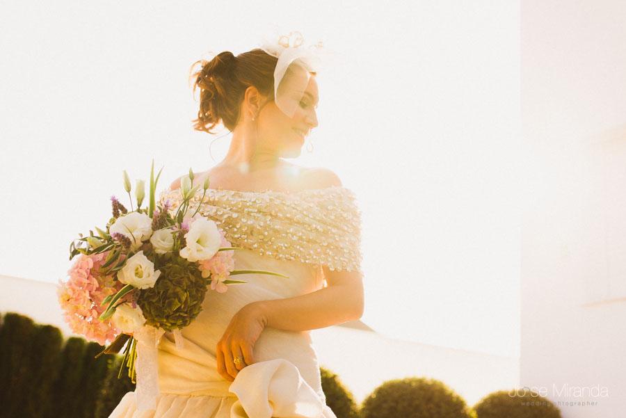 retrato de novia con tocado y  ramo de flores original con el sol por detrás