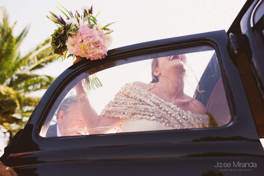 fotografía de novia subiendo al coche nupcial con ramo de hortensias