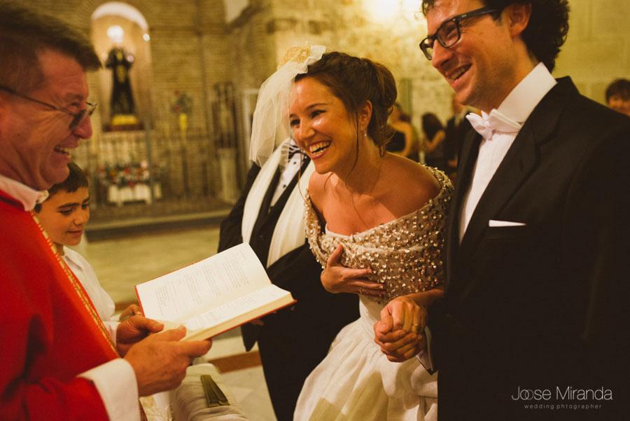 Novios riéndose con el cura durante la ceremonia en la Iglesia de Santa Marta en Martos