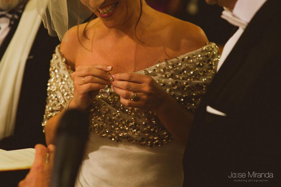 Novia cogiendo el anillo riendose antes de ponerselo al novio en una Boda en Martos