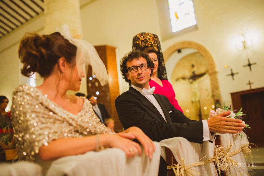 Novio haciendole muecas a la novia para que se ria durante la ceremonia en la Iglesia de Santa Marta