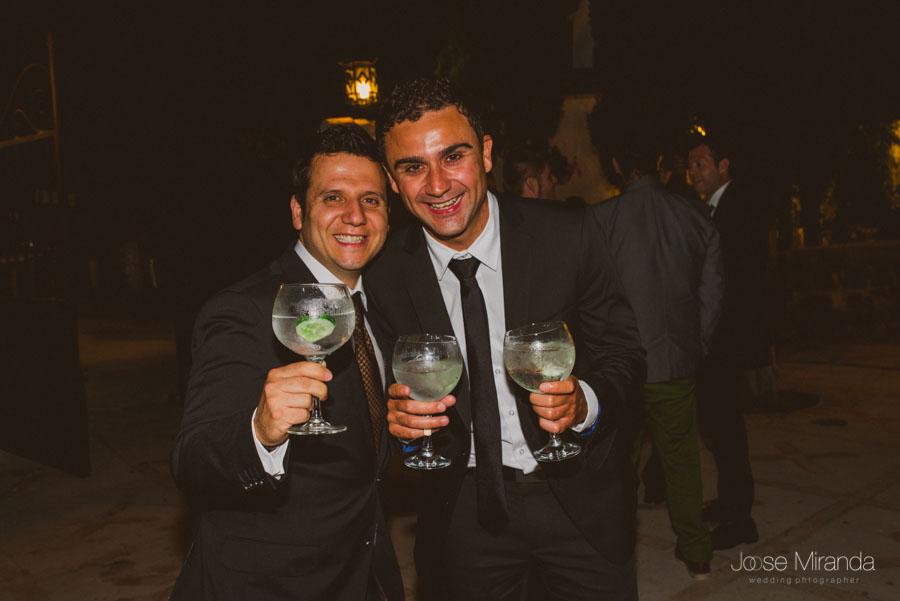 Amigos de los novios en el baile con gin tonics en la mano en una fotografia de boda en El cortijo del Madroño