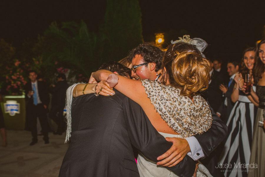 Novios abrazados a sus hermanos durante el baile en una Fotografía de Boda en Martos