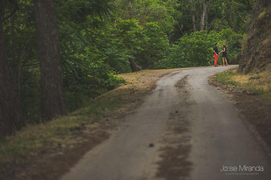 Novios jugando al final del camino del bosque en una fotografía de pre-boda