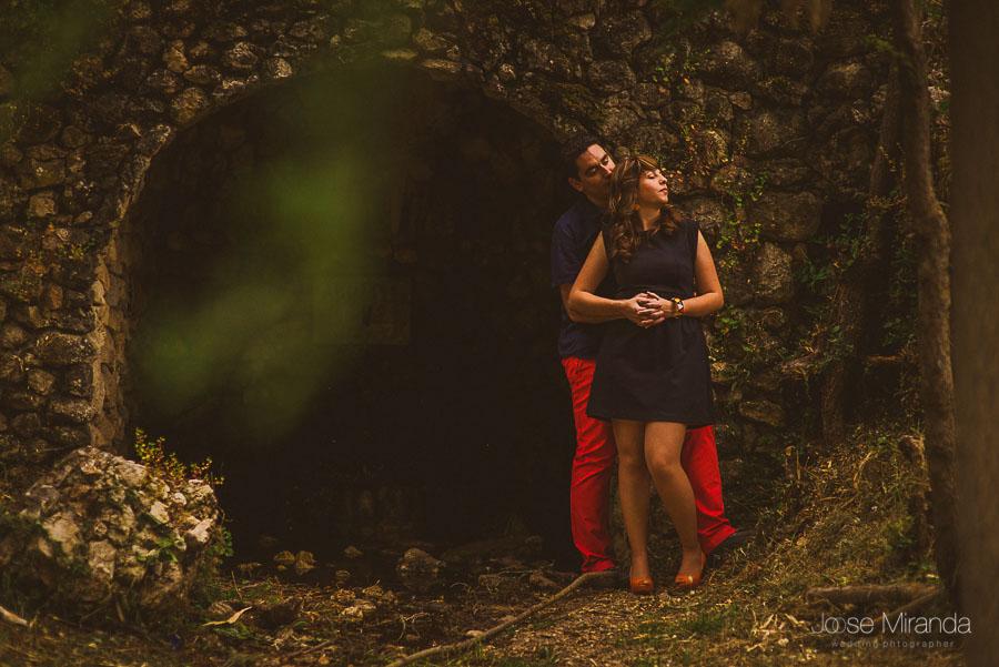 Juan abrazando a Bea al lado de un túnel de piedra en una fotografía de pre-boda en Jaén