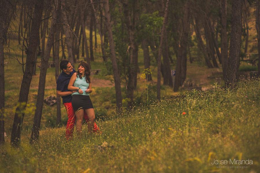 Novio haciendo cosquillas a su novia entre los arboles en un bosque de Jaén en una fotografía de pre-boda de Jose Miranda