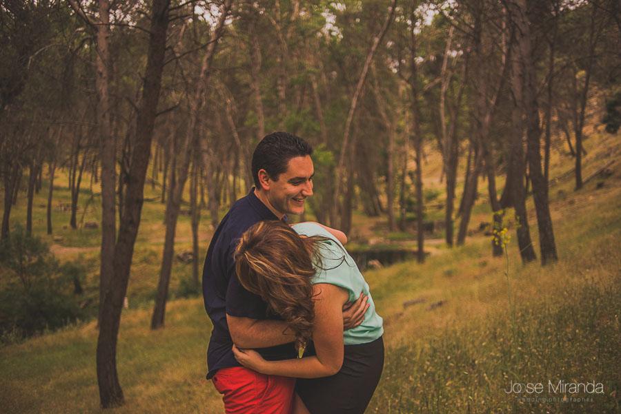 Novios haciéndose cosquillas entre los arboles de Jaén en una fotografía de pre-boda