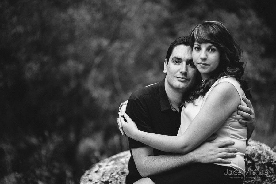 Bea y Juan abrazados con las ramas de los arboles al fondo desenfocadas en una fotografía de pre-boda de Jose Miranda en Jaén