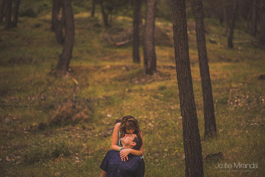 Novia besando al novio con los troncos de los arboles desenfocados al fondo en una fotografía de pre-boda de Jose Miranda en Jaén