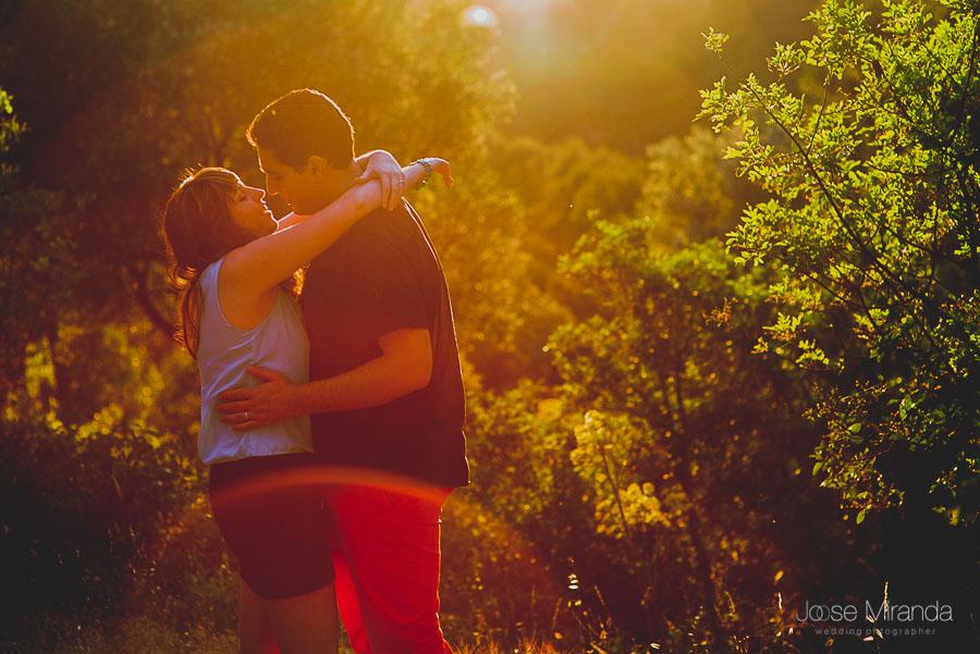 Novios abrazándose con los últimos rayos de sol de la sesión de fotografía de pre-boda