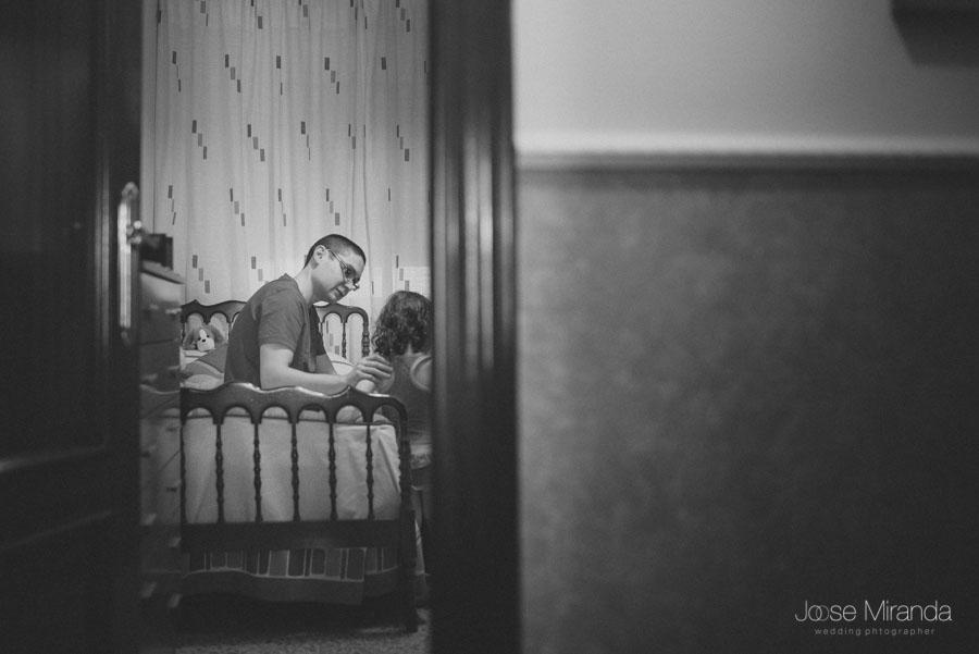 El novio antes de vestirse acariciando a su hija en una fotografía de boda en Martos