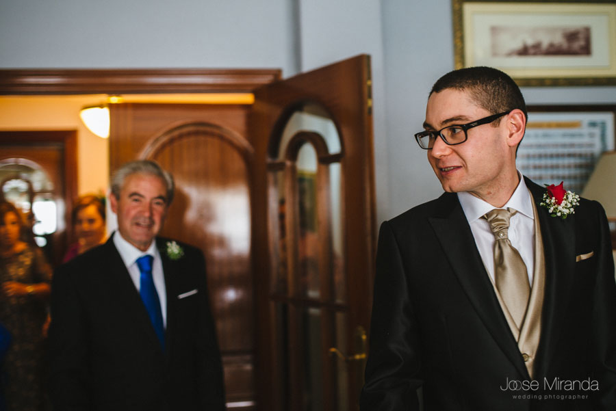 El novio mirandose en el espejo con su padre y más familiares al fondo en una fotografía de boda en Martos
