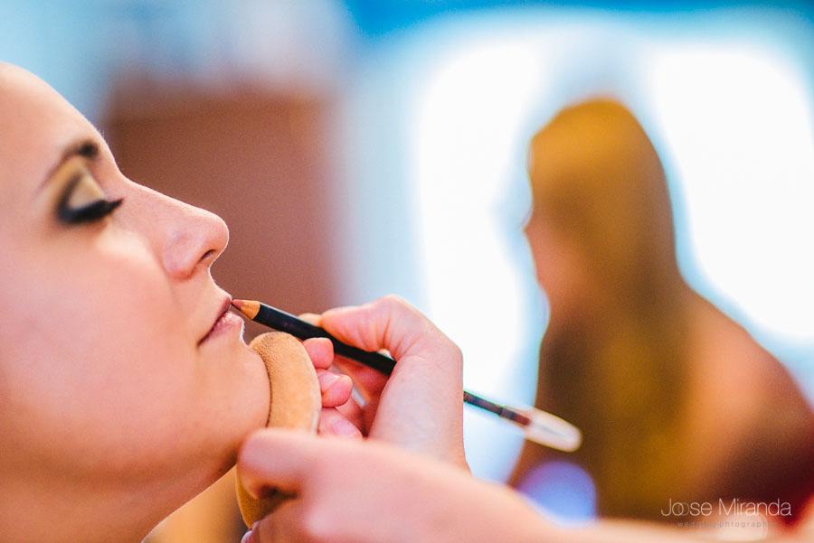 Sombra de la maquilladora en el espejo mientra maquilla los labios de la novia en una fotografía de boda de Jose Miranda