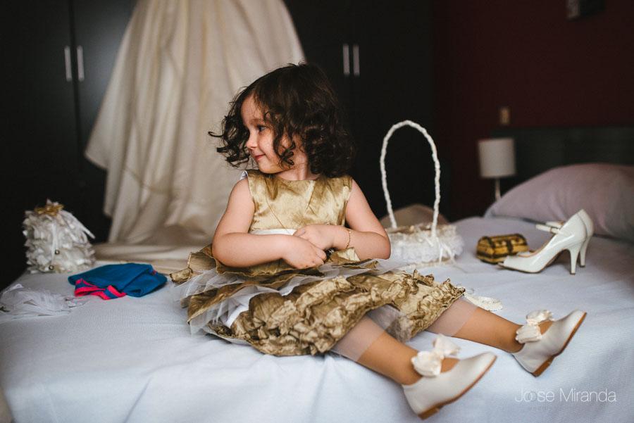La niña de arras y la hija de la novia con los zapatos y el vestido de la novia en una fotografía de boda en Martos