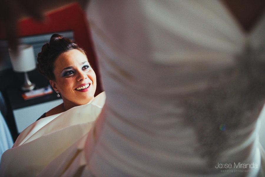 La cara de felicidad de la hermana de la novia arreglando el vestido de novia de Rosa
