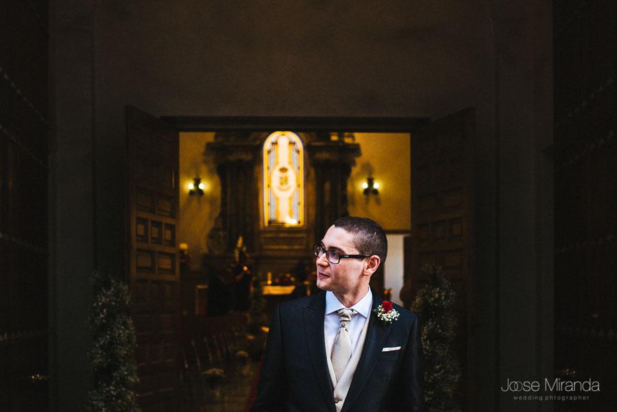Novio asomado a la puerta esperando a la novia en la Capilla del Hospital de San Juan de Dios en Martos