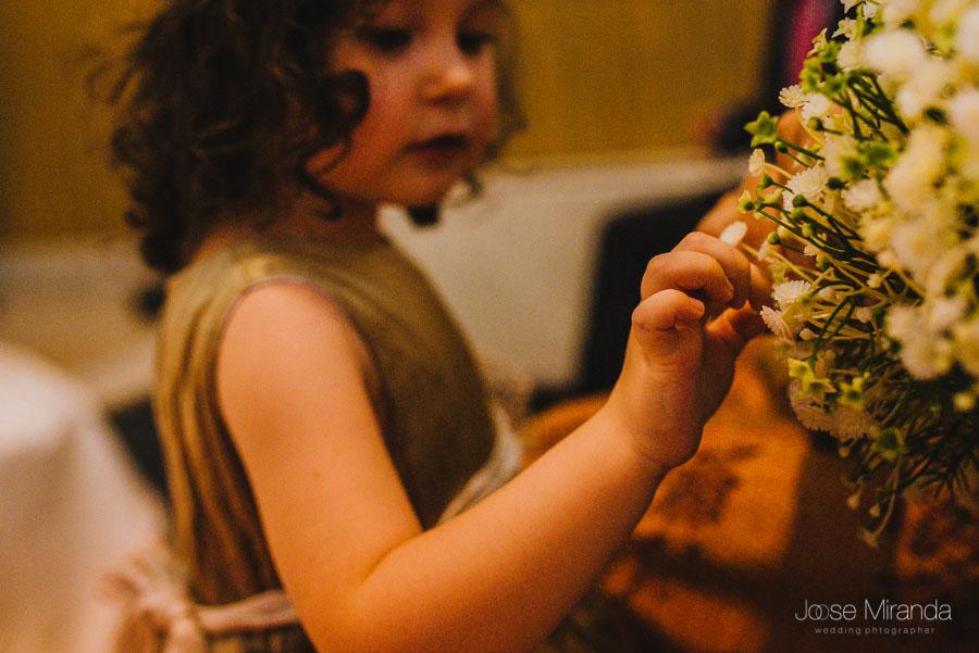 Niña de las arras tocando las flores de la decoración de la capilla en una boda civil