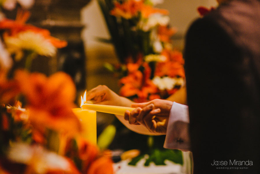 Los novio acercando las velas durante la celebración de la boda civil en la Capilla del Hospital de San Juan de Dios en Martos
