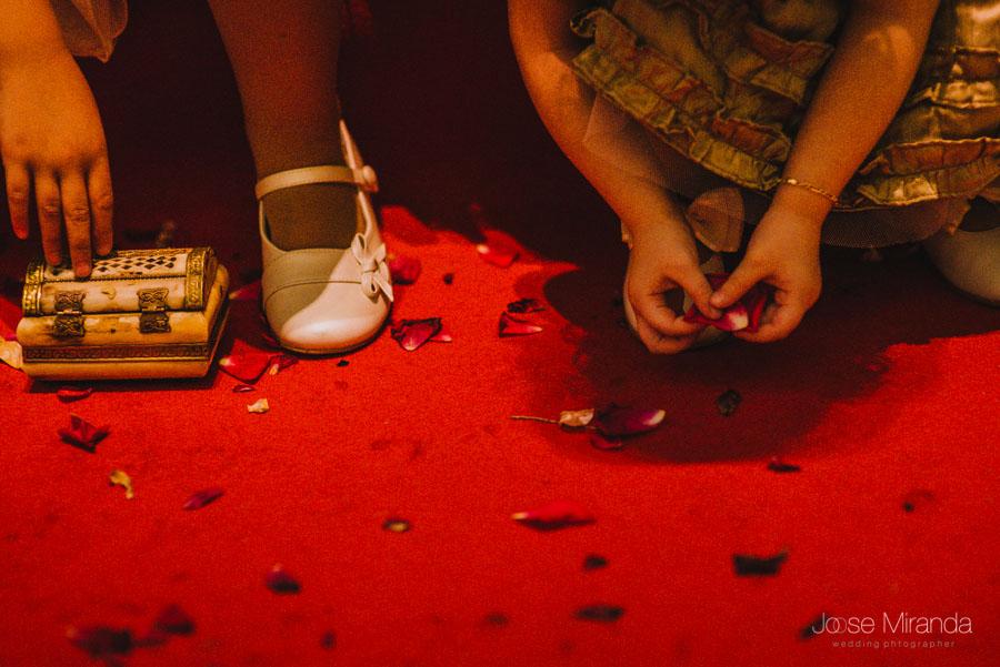Detalle de las manos de las niñas de arras jugando con los petalos