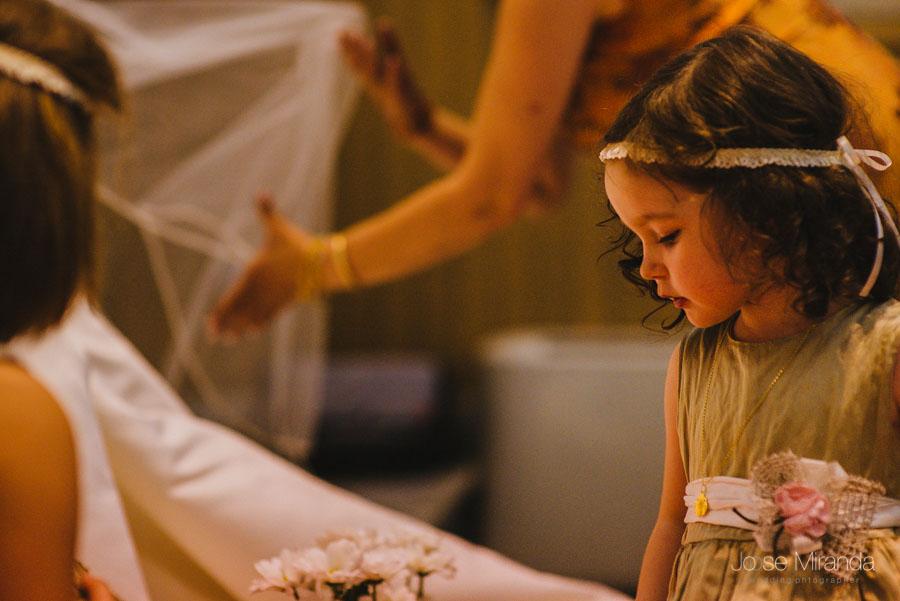 Niña de arras poniendo el velo de la novia bien en una fotografía de boda de Jose Miranda