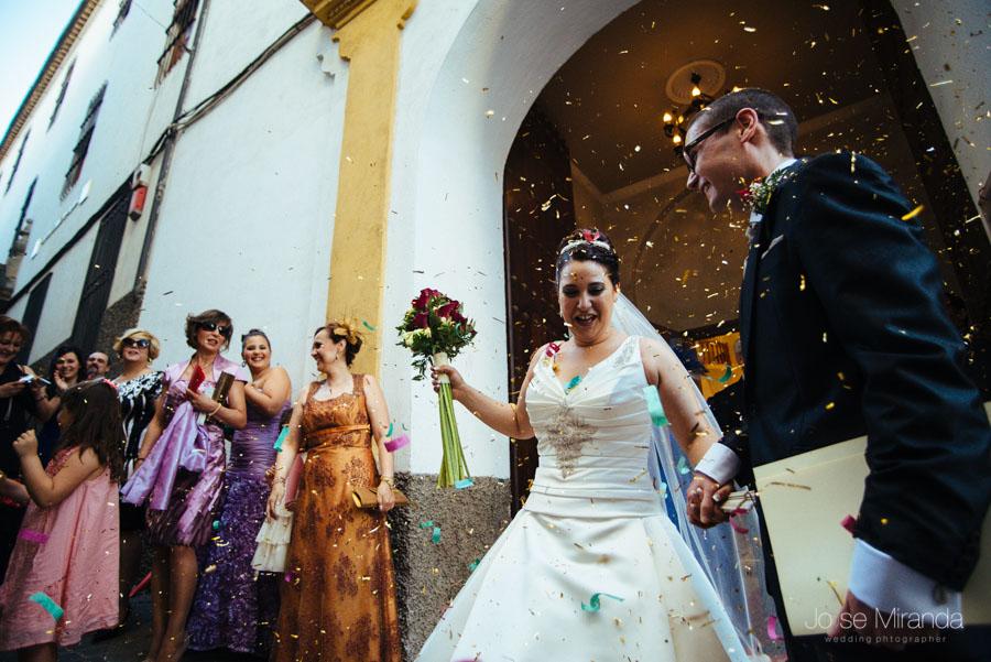 Los invitados tirando el arroz sobre los novios a su salida de la capilla del Hospital de San Juan de Dios en una fotografía de boda en Martos