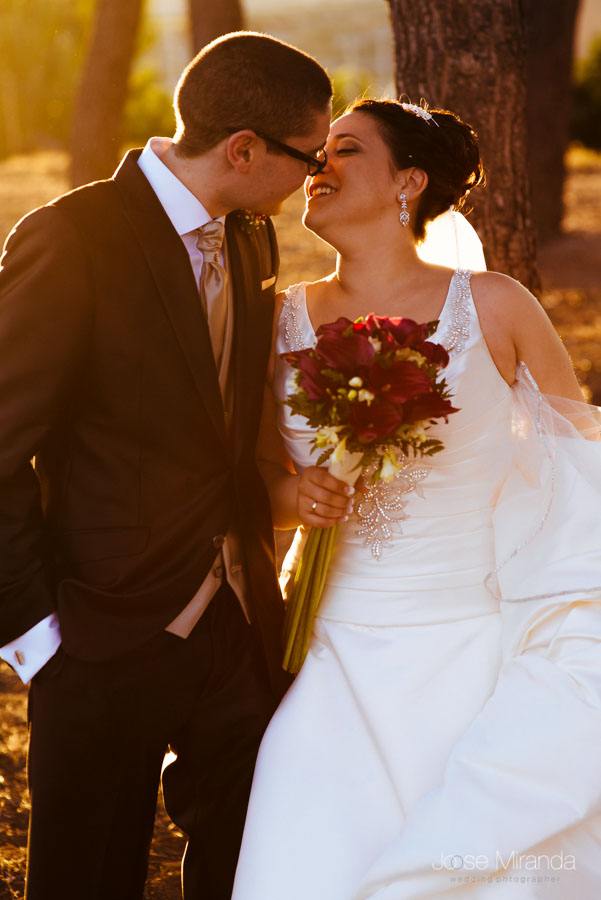 Novia besando a novio a contraluz con el pinar al fondo en una fotografía de boda en Martos