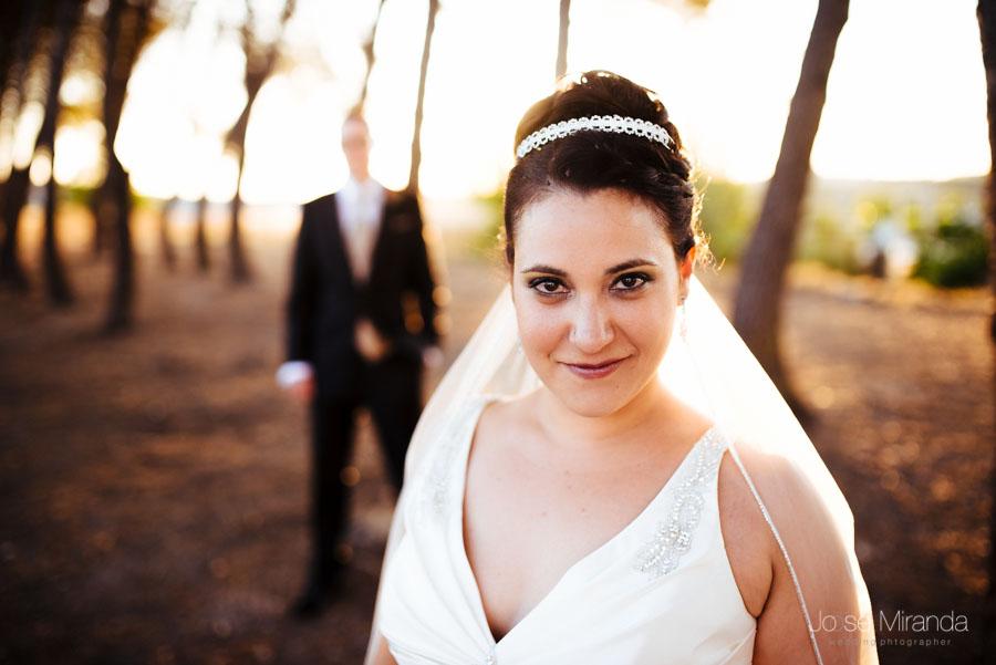 Novia en primer plano y el novio detrás desenfocado con los pinos al fondo en una fotografía de boda civil en Martos