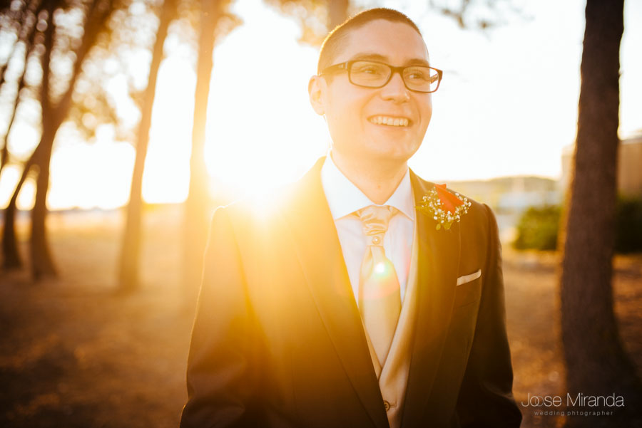 El novio mirando a la novia a contraluz con el sol poniéndose entre los pinos en Martos