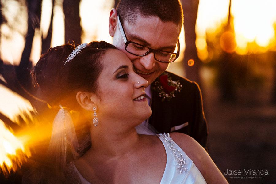 Novios abrazados de espaldas con el sol poniendose y los reflejos de la luz en una fotografía de boda de Jose Miranda