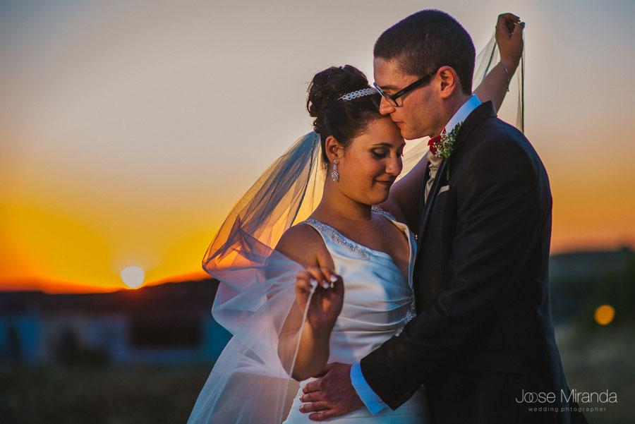 Novia jugando con el velo mientras el novio la besa en la frente y el sol se pone al fondo en una fotografía de boda de Jose Miranda