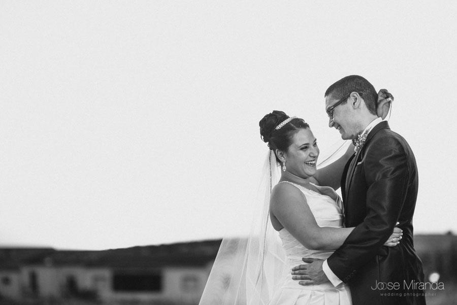Novios riendo mientras se pone el sol en una fotografía de boda de Jose Miranda