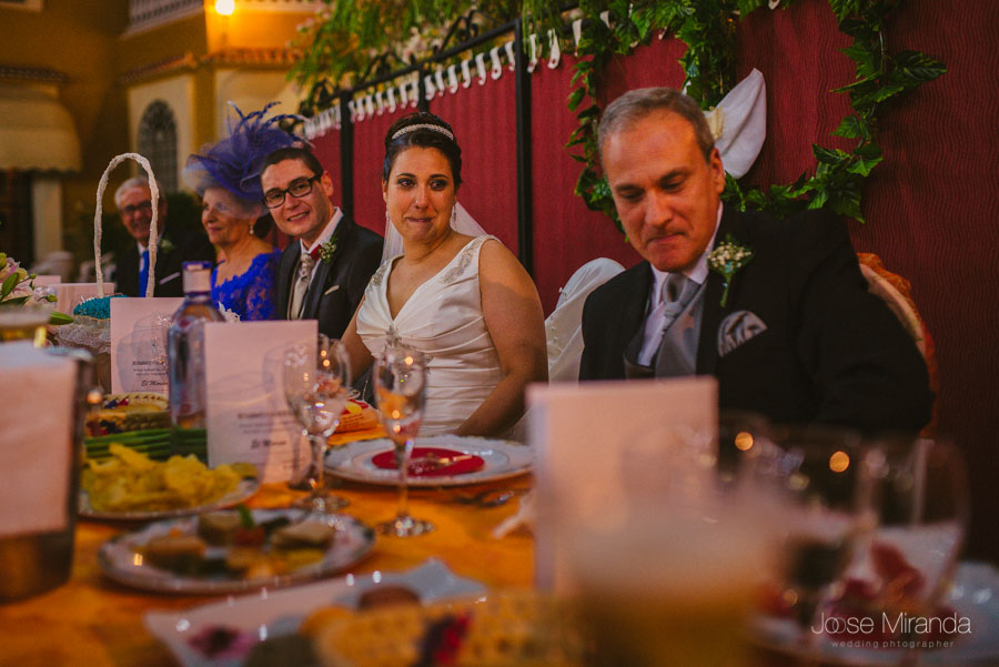 Novios acomodándose a la mesa mirando a su hija