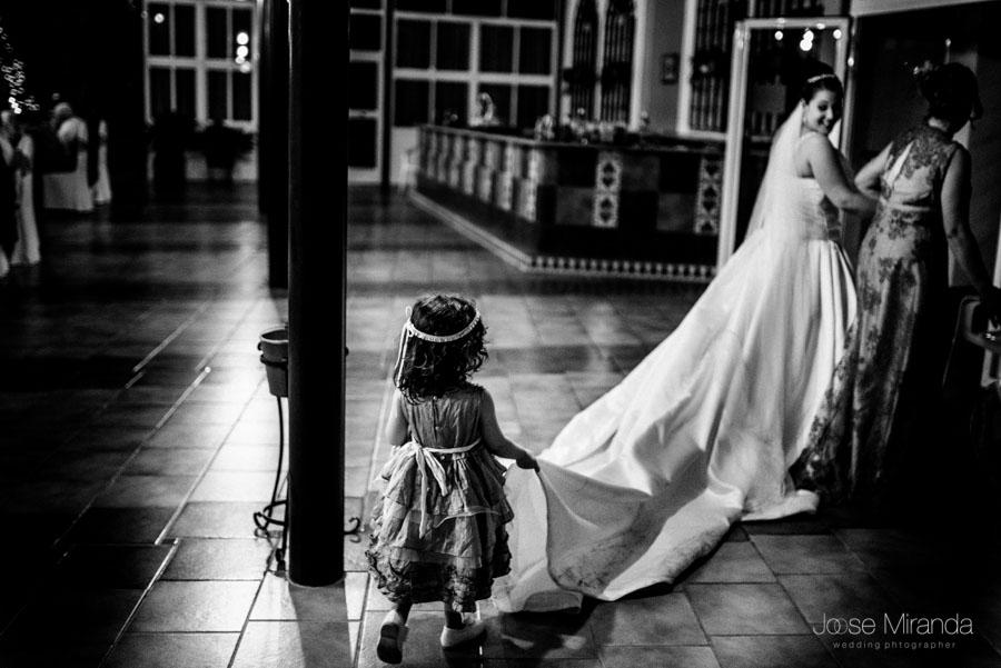 La hija de la novia llevandole el vestido a su madre mientras entra al lugar de la fiesta