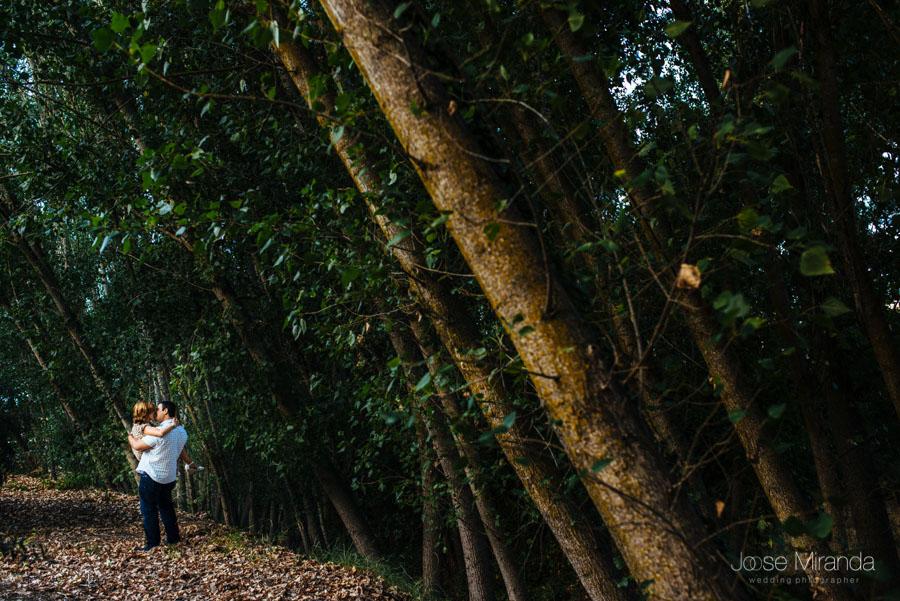 Novio cogiendo a su novia en brazos con un primer plano de los arboles en una fotografía de boda de Jose Miranda