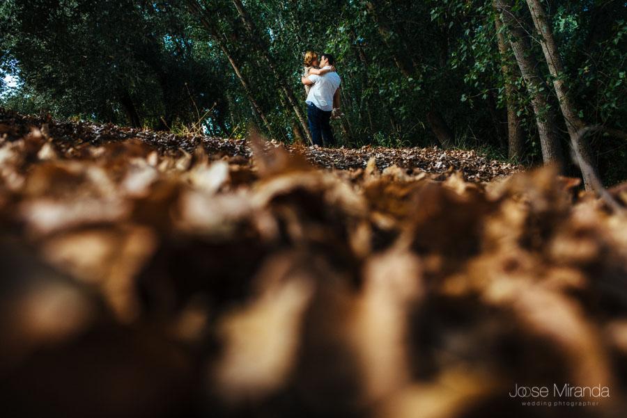 Novio cogiendo a su novia en brazos y besandola con un primer plano de de las primeras hojas caidas de los arbolea