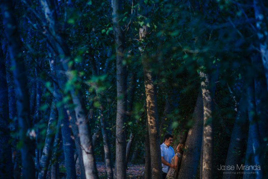 Un rayo de luz ilumina a una pareja de novios entre un sombrío bosque de rivera en una fotografía de boda en Jaén de Jose Miranda