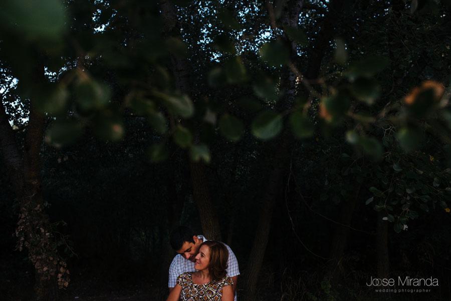 Pareja de novios abrazados bajo las hojas de los arboles en una fotografía de boda en Jaén de Jose Miranda