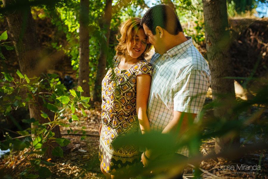 Novia sonriendo con los ojos cerrados mientras su novio la abraza entre los arboles y el sol en una fotografía de boda en Alcaudete de Jose Miranda