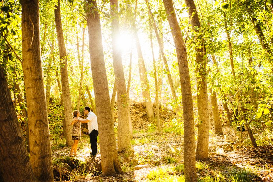 pareja de novios jugando entre los arboles con el sol detrás en una fotografía de boda en Jaén de Jose Miranda