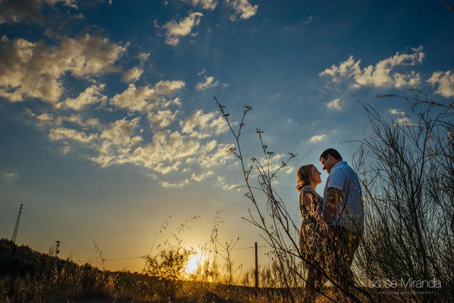 Pareja de novios abrazados contra el sol poniendose y las nubes del atardecer