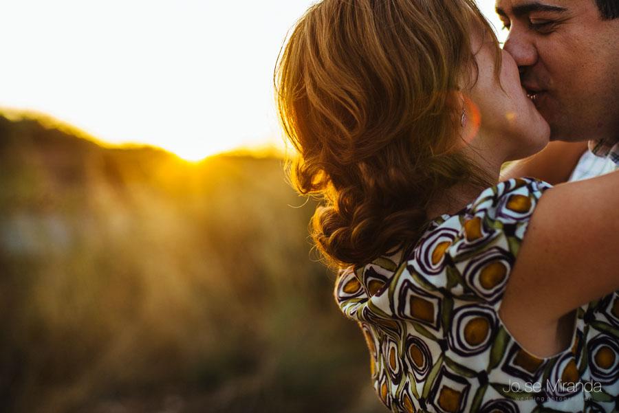 Pareja de novios besándose mientras el sol se pone