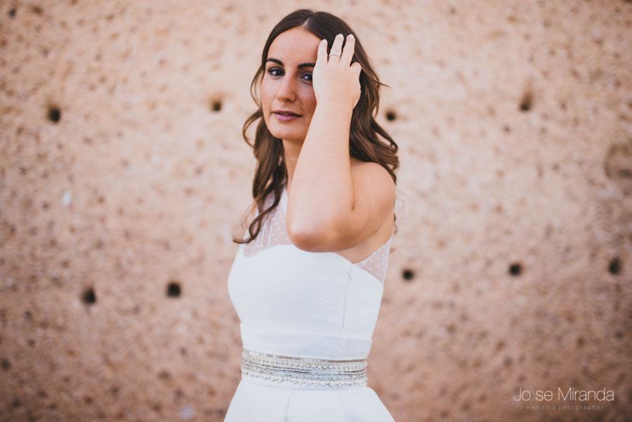 Novia colocandose el cabello ante una pared de piedra en una fotografía de boda en Linares