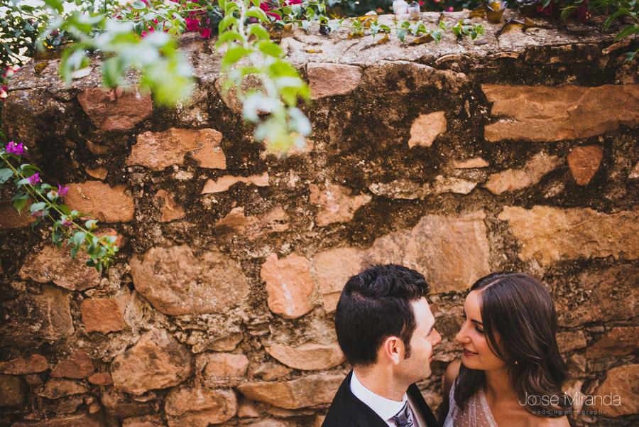 Pareja de novios acercándose para besarse apoyados en una pared de piedra bajo las ramas de una arbol