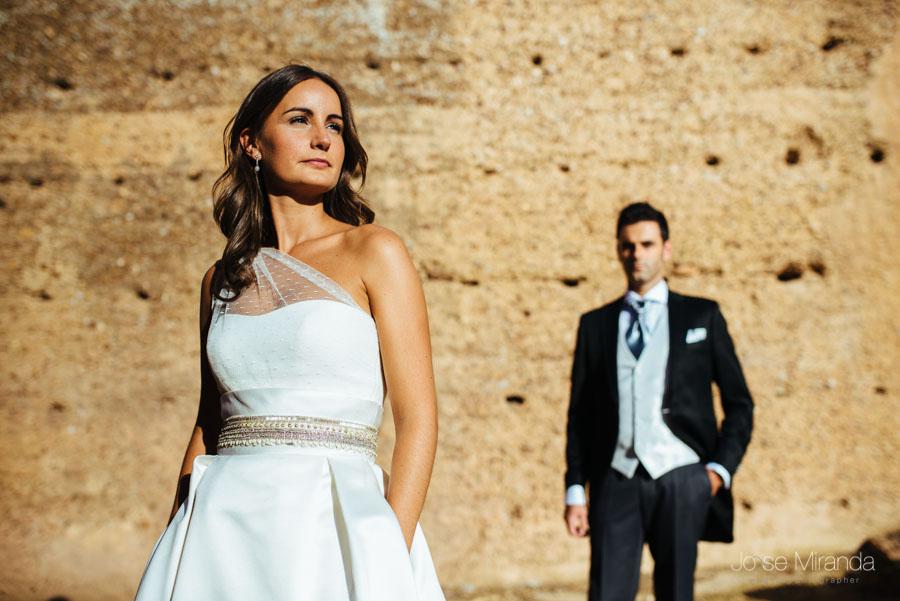 Novia al sol con las mano en los bolsillo del vestido de novia mientras el novio se acerca